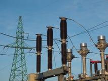 Зеленая опора, высоковольтный автомат защити цепи и настоящие трансформаторы на предпосылке голубого неба стоковые фото