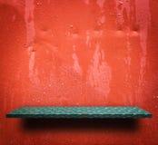 Зеленая пустая полка на красном влажном металле Стоковое Фото