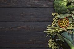 Зеленая рамка макаронных изделий и овощей на предпосылке rustiv деревянной Стоковая Фотография RF
