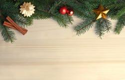 Зеленая рамка рождества с ветвями ели на яркой древесине стоковые изображения rf