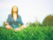 Зеленая трава - йога практики женщины в предпосылке Стоковое фото RF