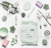 Зеленая установка заботы кожи косметическая с цветками орхидеи, аксессуары и лицевой утихомиривать покрывают маску на белизне стоковое фото rf