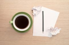 Зеленая чашка кофе на таблице и пустом листе, карандаше, скомканных утилях стоковое изображение rf