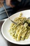 Зеленое блюдо макаронных изделий pesto с вилкой стоковые фото