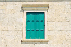 Зеленое окно против стародедовской стены стоковые изображения rf