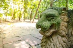 Зеленое пребывание скульптуры льва песчаника стороны самостоятельно в общественном парке стоковое фото