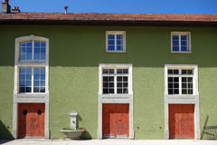 Зеленое традиционное швейцарское здание с красными дверями стоковая фотография