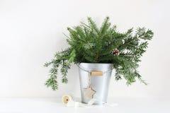 Зеленые ветви ели в металлическом ведре Состав рождества при pinecones, деревянная звезда и катышка ленты лежа дальше Стоковые Изображения RF