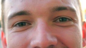 Зеленые глаза молодого уверенно парня моргая и смотря в камеру на улице города Портрет счастливого красивого человека сток-видео
