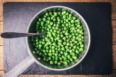 Зеленые горохи на серебряной сковороде Стоковые Изображения