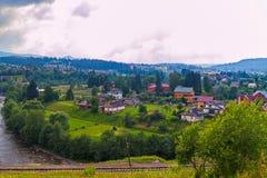 Зеленые деревья, голубые горы, разнообразие крыши домов и белые облака в небе красотка что Стоковые Фотографии RF