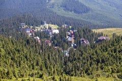 Зеленые ели и дома деревни на фоне прикарпатских гор в лете Украина Стоковое Изображение RF