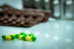 Зеленые, желтые пилюльки капсулы tramadol на запачканном bac пакета волдыря стоковые изображения