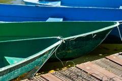 Зеленые и голубые шлюпки весла отдыха связанные к пристани стоковые фотографии rf