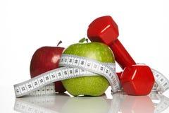 Зеленые и красные яблоки с измеряя лентой и красные гантели Стоковое фото RF