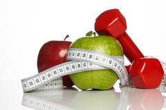 Зеленые и красные яблоки с измеряя лентой и красные гантели Стоковое Фото