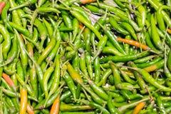 Зеленые и оранжевые chili или перцы для продажи в рынке стоковое изображение