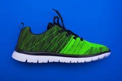 Зеленые и черные ботинки женщины спорта на голубой предпосылке Стоковые Фотографии RF