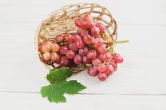 Зеленые лист около свежих зрелых розовых виноградин полили из плетеной корзины на старых деревянных белых планках Стоковые Фото