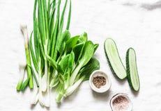Зеленые луки, чеснок, bok choi капусты, огурцы - свежие зеленые овощи на белой предпосылке, взгляд сверху скопируйте космос Стоковые Фотографии RF