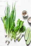Зеленые луки, чеснок, bok choi капусты, огурцы - свежие зеленые овощи на белой предпосылке, взгляд сверху скопируйте космос Стоковые Изображения RF
