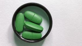 Зеленые овальные пилюльки в крышке на белой предпосылке Стоковые Фотографии RF