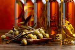 Зеленые оливки и бутылки оливкового масла с warious специями и им Стоковые Изображения RF