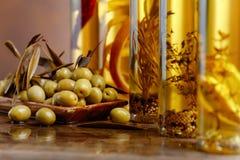 Зеленые оливки и бутылки оливкового масла Стоковые Изображения