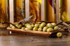 Зеленые оливки и бутылки оливкового масла Стоковая Фотография