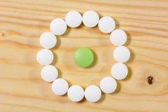 Зеленые пилюльки в круге белых пилюлек Стоковые Изображения RF