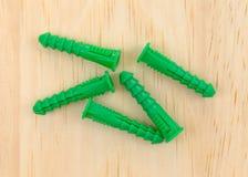 Зеленые пластичные анкеры гипсокартона на сосне всходят на борт Стоковые Изображения RF