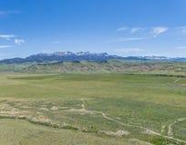 Зеленые равнины и скалистые горы стоковая фотография
