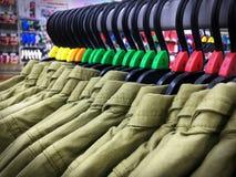 Зеленые рубашки на вешалках с ярлыками номера размера в магазине одежды стоковая фотография