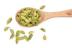 Зеленые семена кардамона в деревянной ложке изолированной на белой предпосылке Взгляд сверху Положение плоское Стоковое Изображение