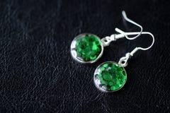 Зеленые серьги смолы на темной предпосылке Стоковая Фотография