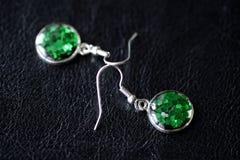Зеленые серьги смолы на темной предпосылке Стоковое Фото