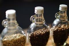 Зеленые фасоли и кофейные зерна внутри ясной бутылки, onl фокуса Стоковое фото RF