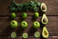 Зеленые цвета мустарда, лимон, авокадо и зеленое яблоко аранжировали на деревянном столе Стоковые Фото
