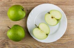 Зеленые яблоки и половины яблока в плите на таблице Стоковые Изображения
