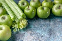 Зеленые яблоки и сельдерей на голубой конкретной предпосылке Программа вытрезвителя, план диеты, потеря веса Горизонтальный плоск стоковое изображение rf