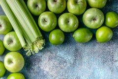 Зеленые яблоки, сельдерей и известки на конкретной предпосылке Программа вытрезвителя, план диеты, потеря веса r r стоковые фото