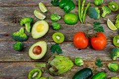 Зеленые smoothie и ингридиенты - авокадо, яблоко, огурец, киви, лимон, укроп, сельдерей, брокколи, деревянная доска, Стоковое Изображение
