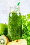 Зеленые smoothies от петрушки, салата, кивиа, яблока в бутылке на серой конкретной таблице стоковое изображение