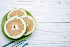 Зеленый грейпфрут на зеленой плите на белой предпосылке Стоковое Фото