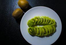 Зеленый зрелый тропический киви на плите на предпосылке темной черноты Стоковое фото RF