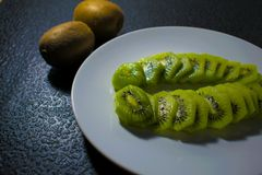 Зеленый зрелый тропический киви на плите на предпосылке темной черноты Стоковые Фото