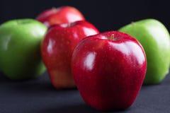 Зеленый и красный цвет яблок на черной предпосылке ткани Стоковые Фотографии RF
