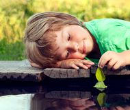 Зеленый лист-корабль в руке детей в воде, мальчике в игре парка с шлюпкой в реке стоковое изображение