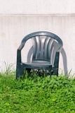Зеленый пластичный стул на траве каменной стеной Стоковые Изображения RF