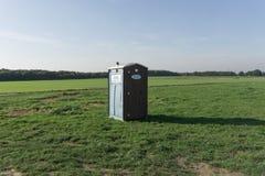Зеленый пластичный туалет в середине пустого зеленого поля стоковая фотография